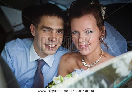 Portrait Of A Newlywed Couple In A Car