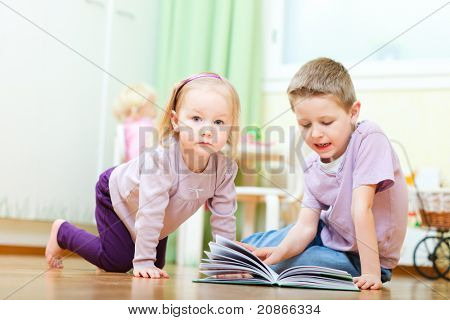 Two little kids playing together in kids room