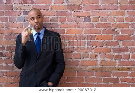 Young Business Man Thinking And Holding A Glass Of Wine