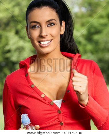 Beautiful young woman jogging in citypark, smiling.?