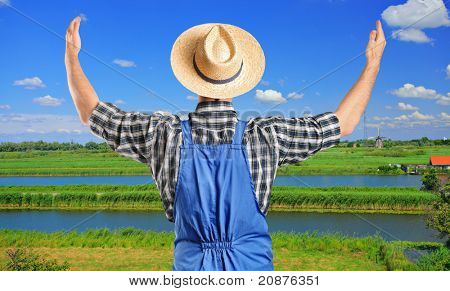 A male farmer gesturing with raised hands with field in the background