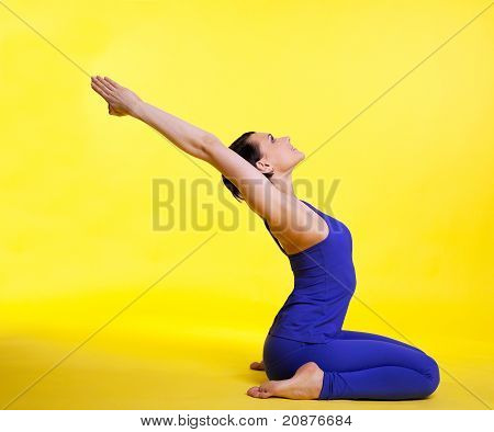 Yong woman doing yoga asana - pigeon pose