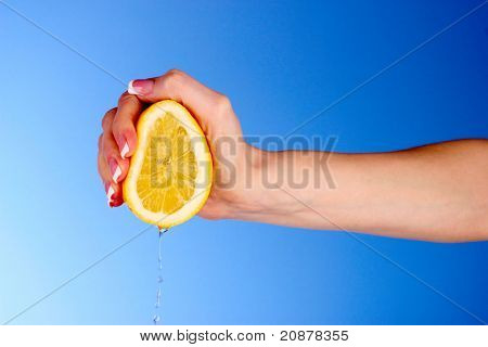 Someone squeeze lemon on a blue background