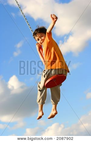 Young Boy On Chain Swing One Arm Raised
