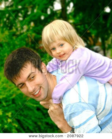 Toddler Girl On Her Fathers Back Outdoor In Park