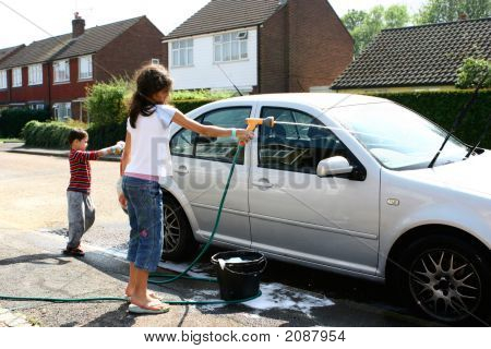 Two Young Children Washing Car