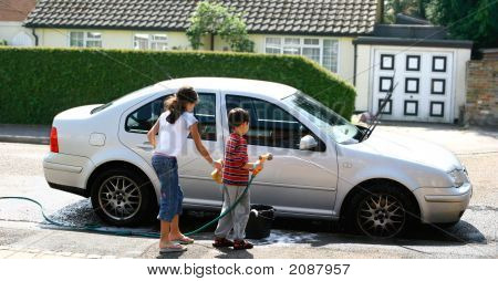Two Young Children Washing  Car In Summer