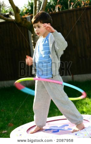Young Boy With Hula Hoop Balanced On His Hip