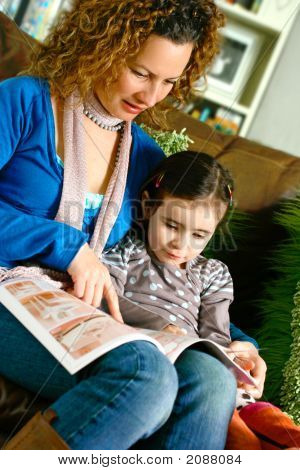 Young Mother Showing A Book To Her Daughter