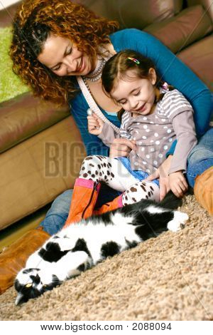 Little Girl And Her Mom Playing With Pet Cat