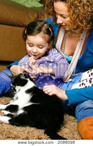 Beautiful Young Girl With Her Mom Stroking Pet Cat
