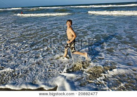 Young Boy Enjoys The Waves Of The Blue Sea