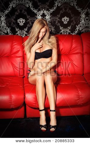Bashful Young Blonde Lady In Black Lingerie Sitting On Red Leather Sofa
