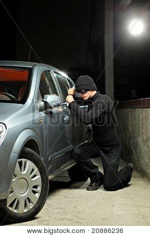 Un ladrón con una máscara de robo tratando de robar un coche