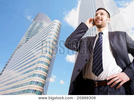 Businessman with cellphone on a background of skyscrapers