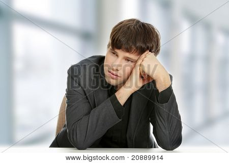 Businessman in depression, with hand on forehead.