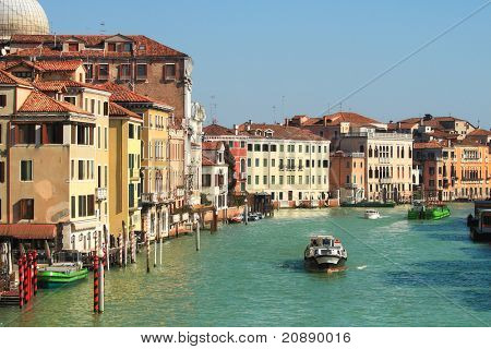 View on motor boat on city canal passing by old historic multicolored houses in Venice, Italy.