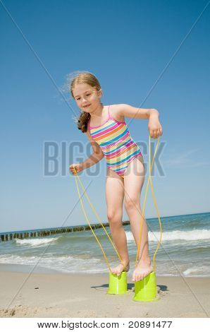 Summer vacation - little girl  playing with bucket stilts on the beach