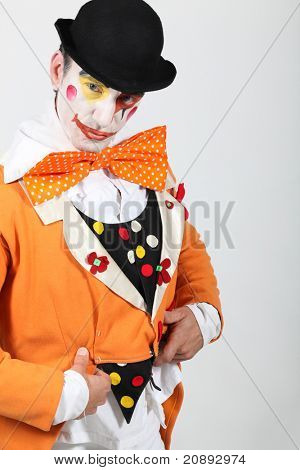 man maked up wearing a grotesque clown costume and a bowler