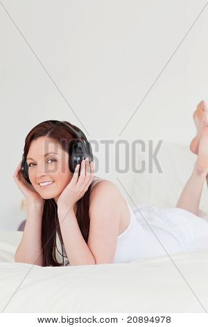 Beautiful Red-haired Female Relaxing With Her Headphones While Lying On Her Bed