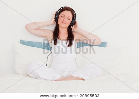 Happy Red-haired Woman Listening To Music With Her Headphones While Sitting On Her Bed