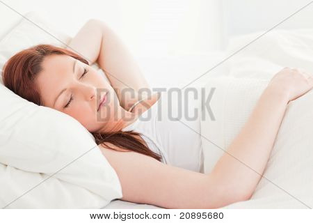 Close-up Of A Cute Red-haired Woman Sleeping In Her Bed