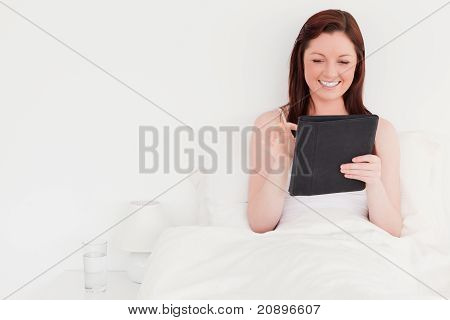 Beautiful Red-haired Woman Relaxing With Her Tablet While Sitting On Her Bed