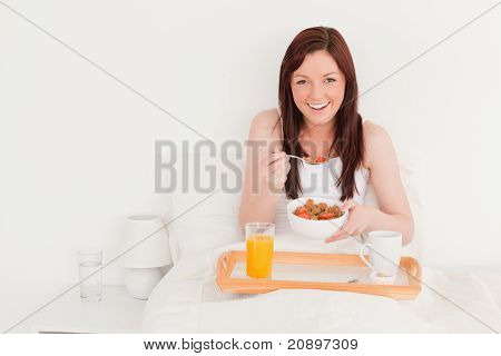 Pretty Red-haired Female Having Her Breakfast While Sitting On Her Bed