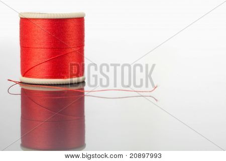 Red Spool Of Thread On A Table