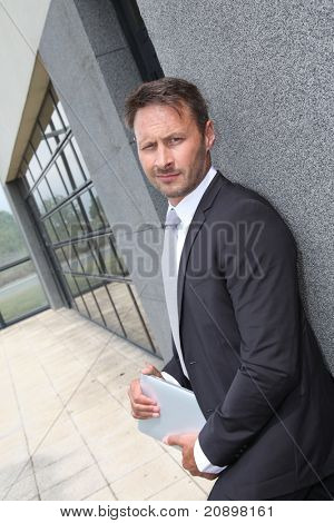 Businessman using electronic tablet outside offices building