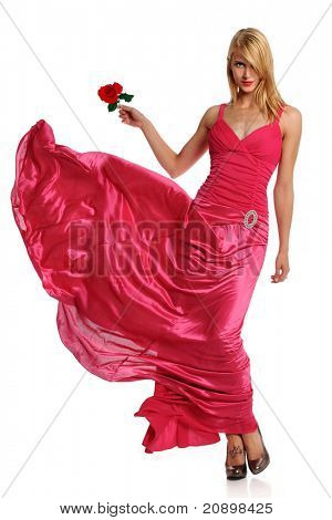 Portrait of beautiful young woman in pink evening gown holding rose