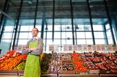 stock photo of grocery store  - Portrait of a grocery store clkerk or owner in front of a vegetable counter - JPG