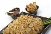 foto of pancit  - Pancit on a ceramic dish with egg rolls and sweet and sour sauce