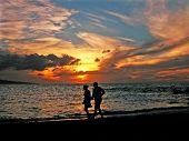 stock photo of beach sunset  - couple walks the beach at sunset - JPG