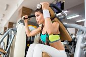 Athletic young woman wearing top and leggings doing exercise on gym machine while having intensive t poster