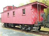 foto of caboose  - Old red caboose sits in repose on old rail line - JPG