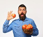 Farmer With Surprised Face Holds Red Apple. poster