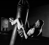 The Boxer In The Gym Hung On A Boxing Bag And Makes Twists For The Abdominal Muscles. poster