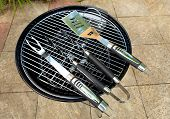 stock photo of meals wheels  - a traditional style bbq with tools placed on it brand new and unlit - JPG