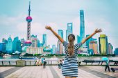 Happy success person with arms up against Shanghai skyline on The Bund. China travel concept or urba poster