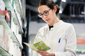 Low-angle portrait of an experienced female pharmacist checking the medical prescription of a pharma poster