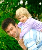 Toddler Girl On Her Fathers Back Outdoor In Park poster