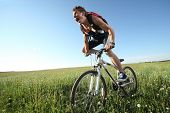 Young roaring man riding on bicycle through deep grass with exertion