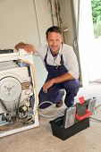 stock photo of washing-machine  - Plumber fixing washing machine - JPG
