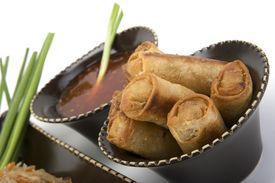stock photo of lumpia  - Pancit on a ceramic dish with egg rolls and sweet and sour sauce - JPG
