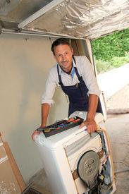 stock photo of washing machine  - Plumber fixing washing machine - JPG