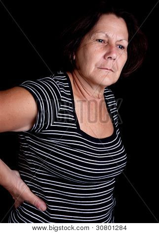 Aged woman suffering from back pain on a black background with space for text