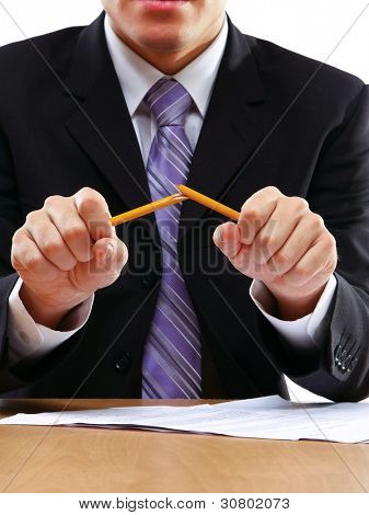 Empresário irritado quebrando lápis isolado