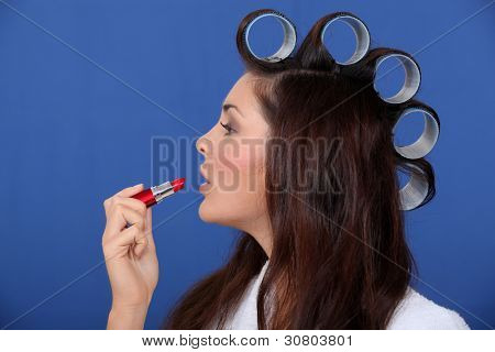 Woman with hair rollers applying lip-stick
