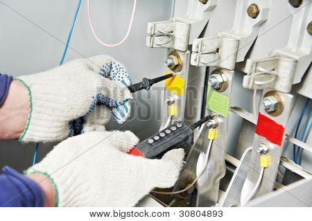 Closeup hands of electrician builder at work with tester measuring high voltage of power electric line in electical distribution fuseboard